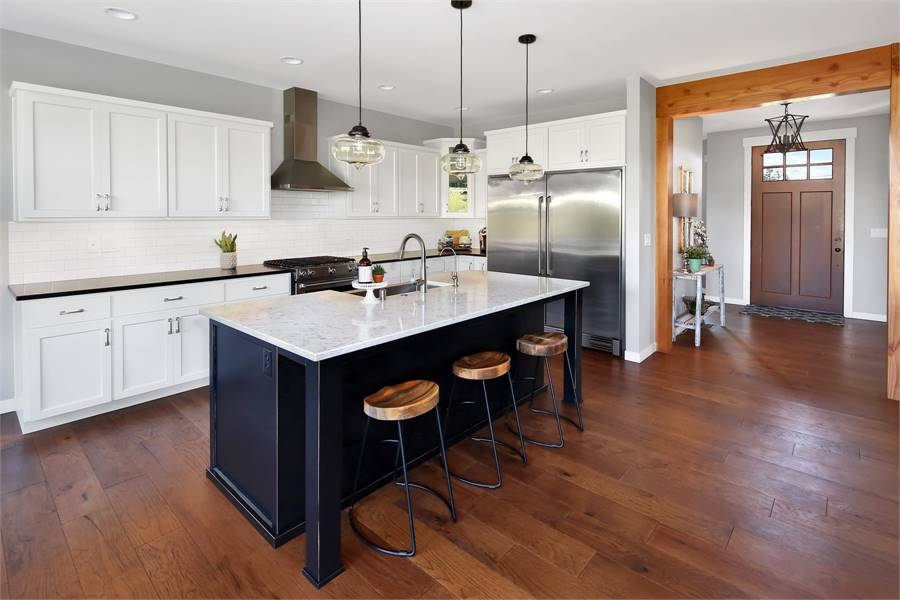 This is a look at the kitchen with a hardwood flooring contrasted by the white cabinetry and the white countertop of the black kitchen island across from the stainless steel fridge.