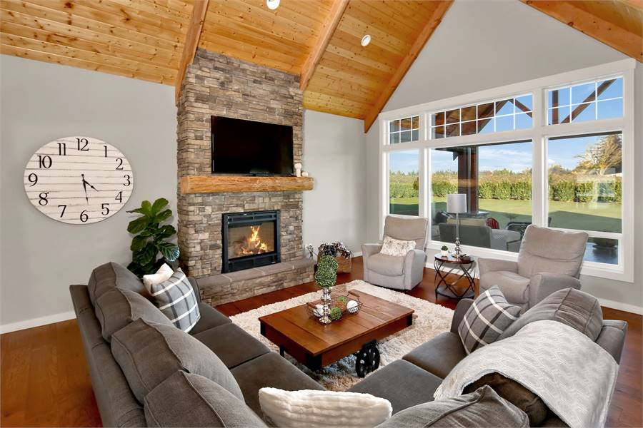 This Northwest-style living room has a tall cathedral ceiling that matches the wooden shelf above the fireplace that stands out with its stone textured panel across from the L-shaped gray sectional sofa.