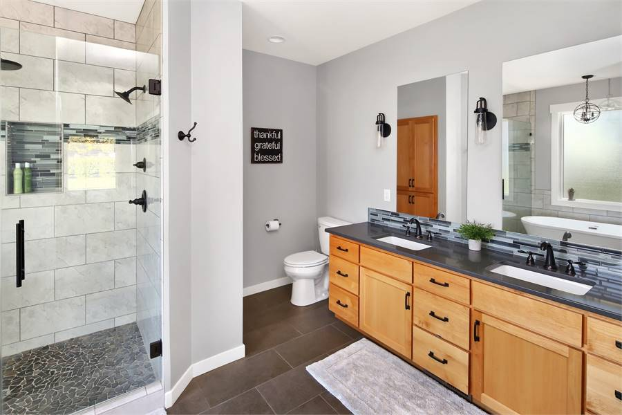 This is a view of the bathroom that has a large two-sink vanity with wooden drawers. Next to this is the toilet at the far corner beside the glass door of the shower area.