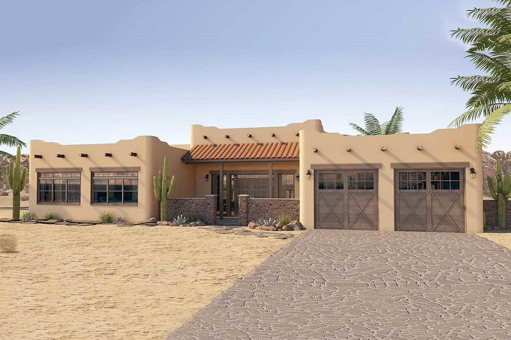This is a look at the single story adobe house with an earthy beige tone to its exterior walls complemented by the exposed wooden beams and mosaic stone driveway.