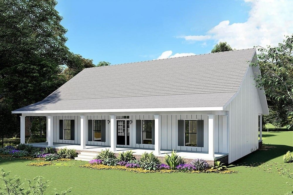 This is a large single-story country farmhouse-style home with a large front porch with pillars and large windows complemented by the shrubs flanking the steps.