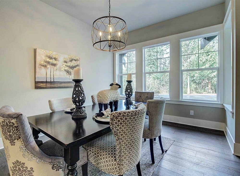 This is a close look at the dining room with a dark wooden rectangular dining table topped with a drum pendant light brightened by the windows.