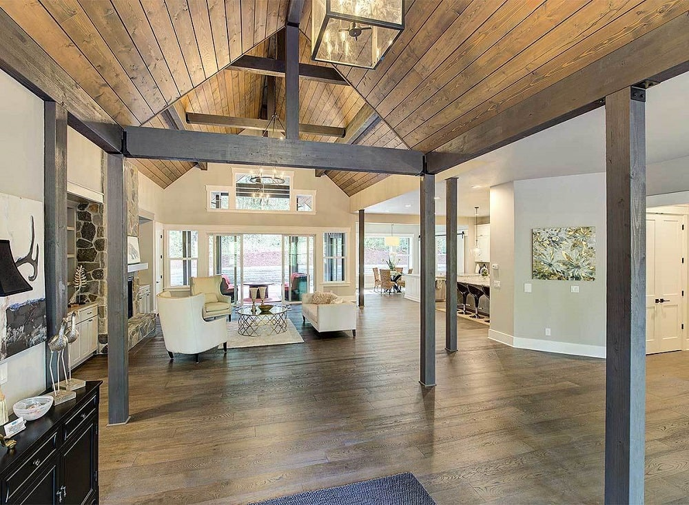 This is a close look at the foyer with a wooden shiplap cethedral ceiling with thin columns and views of the living room.