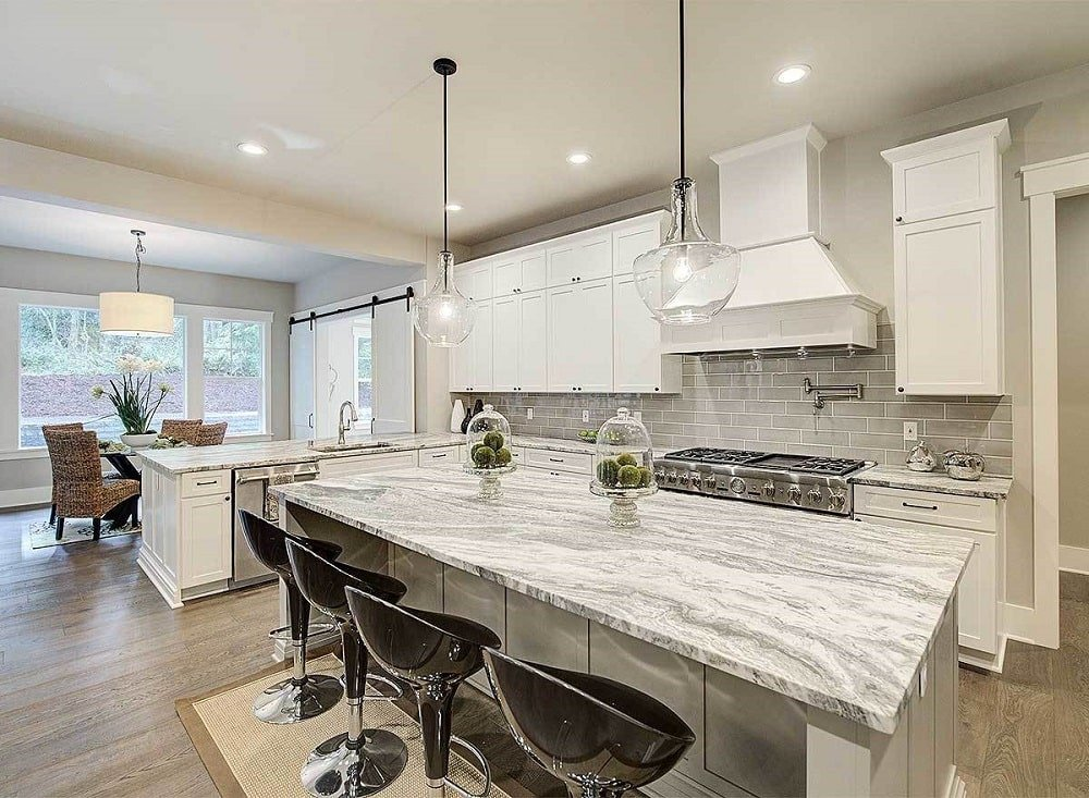 This kitchen has bright white cabinetry that is complemented by the light gray subway tiles and the white marble countertops contrasted by the black modern stools.