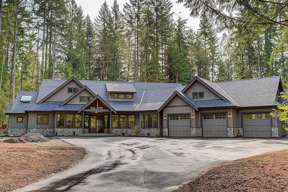 This is a front exterior look at the house that has a large driveway and a background of tall pine trees behind the house.