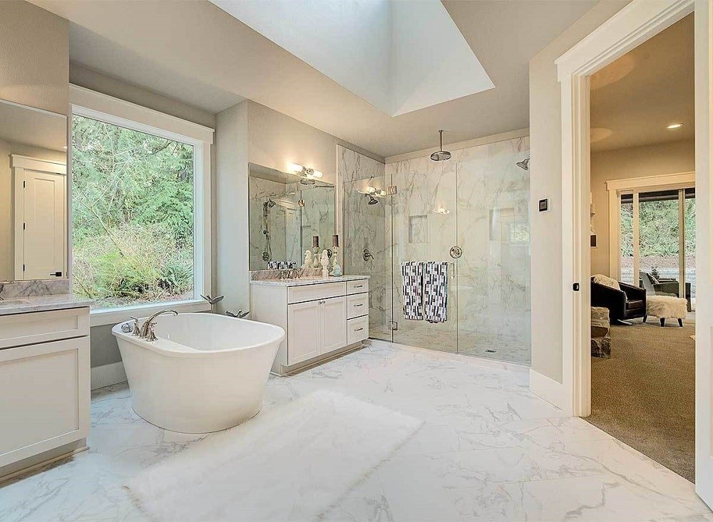 This is the bright bathroom with a freestanding bathtub in the middle of two white vanities and a glass-enclosed shower area on the far side.
