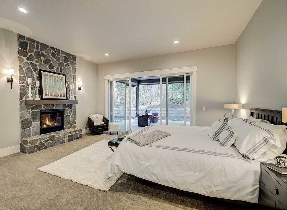 This spacious and bright bedroom has beige walls and ceiling that match the bed across from the stone fireplace adorned with a framed artwork.