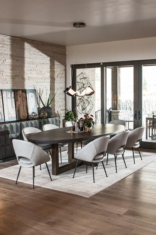The dining room has a large dark wooden elliptical dining table paired with modern gray chairs and topped with a decorative pendant light brightened by the glass doors.