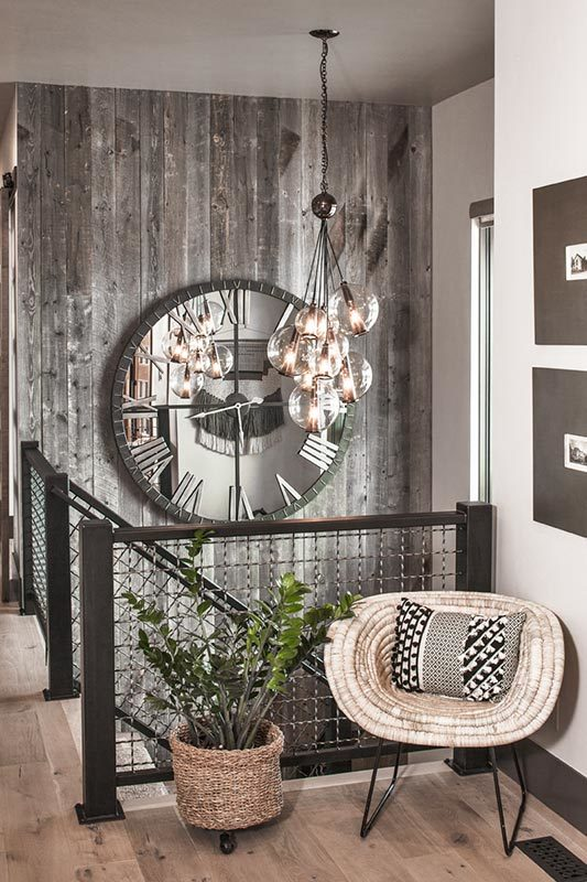 The foyer has a simple chair and potted plant next to the staircase that is adorned with a large wall clock and decorative lighting.
