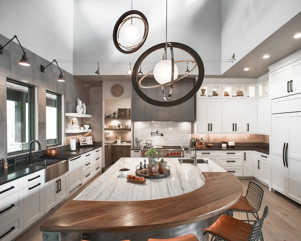 This Northwest-style kitchen is dominated by the large central kitchen island topped with a couple of decorative pendant lights and surrounded by white shaker cabinets and stools.