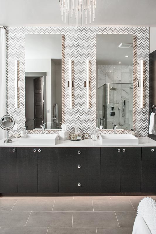 This is a close look at the primary bathroom that has a two-sink vanity with dark cabinets topped by large mirrors across from the glass-enclosed shower area.