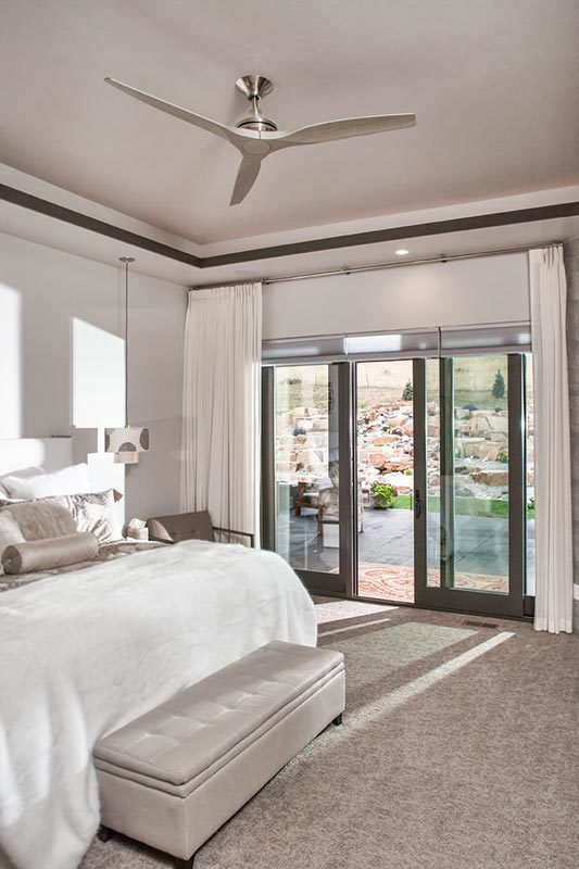 The primary bedroom has a large white bed with a cushioned bench at the foot. There is a set of sliding glass doors at the side of the bed that leads to the outdoor areas of the house.