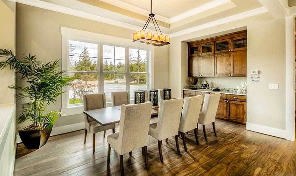 This is the dining room with a long rectangular dark wooden dining table surrounded by beige cushioned chairs and topped with a decorative chandelier hanging from a beige ceiling.