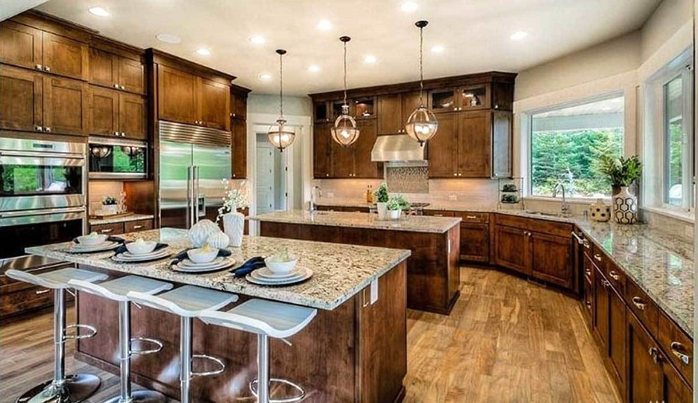 This spacious kitchen has two kitchen islands with the same dark wooden cabinetry as those lining the walls that match well with the hardwood flooring.