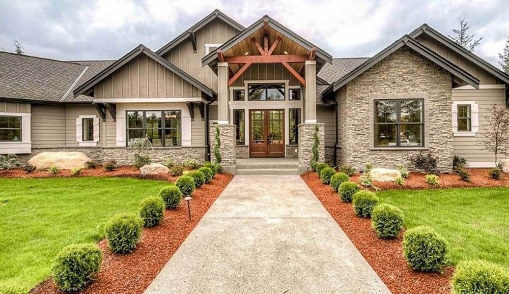 This is a close look at the main entrance of the house with concrete walkway flanked by rows of shrubs and grass lawns on both sides.