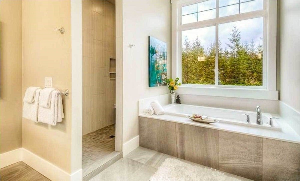 This is a close look at the bathroom with a large bathtub under the window next to the entrance of the walk-in shower area.