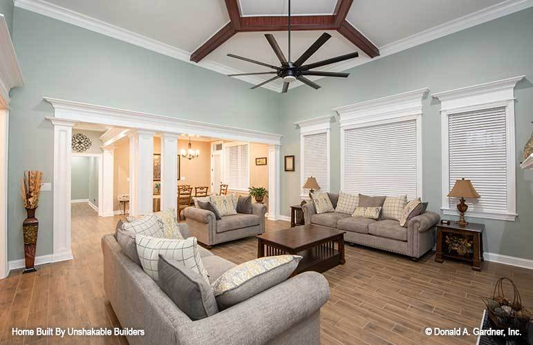 The living room has gray seats, dark wood tables, and three framed windows covered in white blinds.