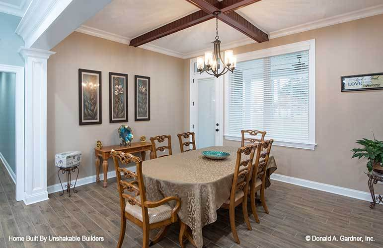 Formal dining room with an oval dining set and a wooden buffet table adorned with framed artworks.