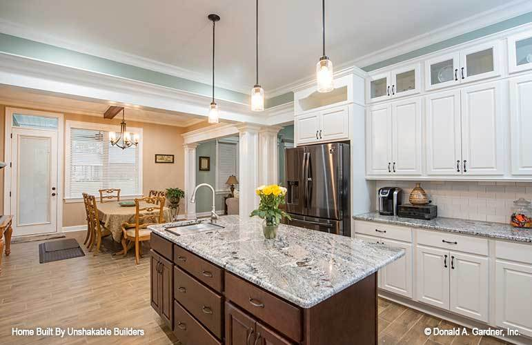 The kitchen is equipped with stainless steel appliances, white cabinetry, granite countertops, and a prep island fitted with a sink.