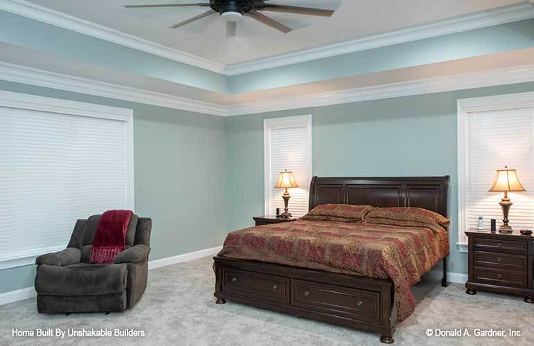 Primary bedroom with carpet flooring, muted green walls, and a tray ceiling mounted with a fan.