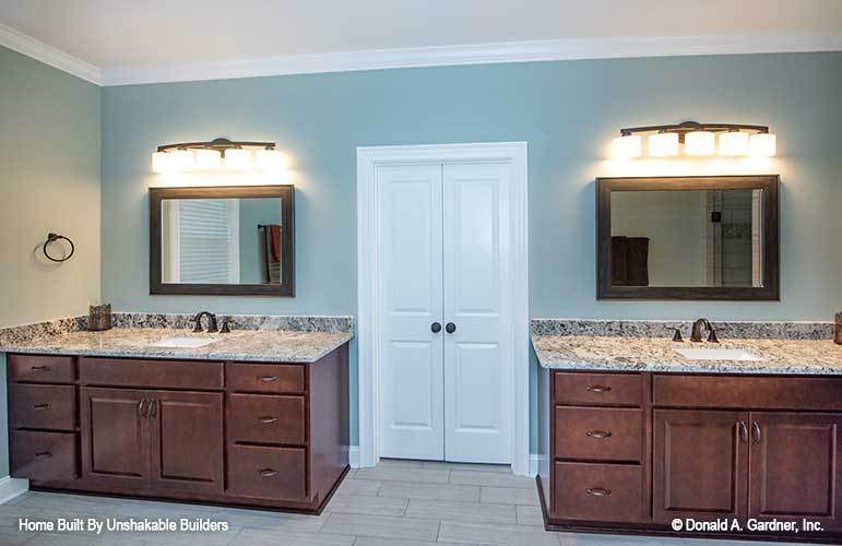 The primary bathroom features his and her vanities flanking a white double door that opens to the walk-in closet.