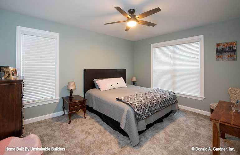 This bedroom is furnished with a dark wood bed, matching nightstands, a wooden dresser, and a desk.