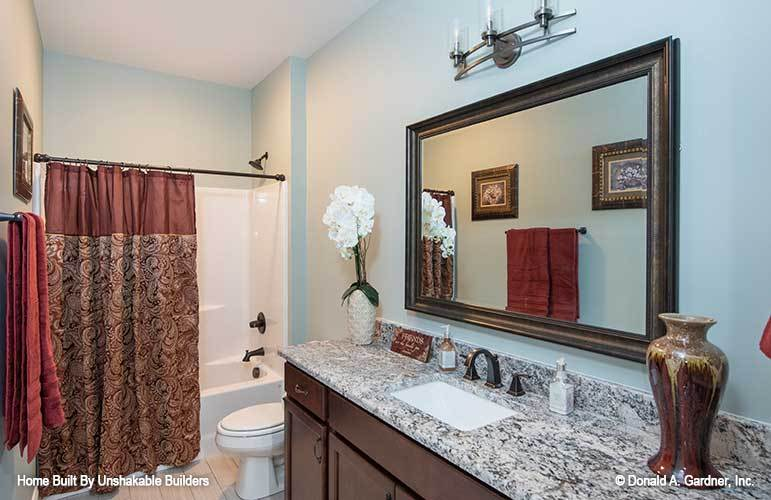 Bathroom with a sink vanity, a toilet, and a tub and shower combo enclosed in a patterned curtain.