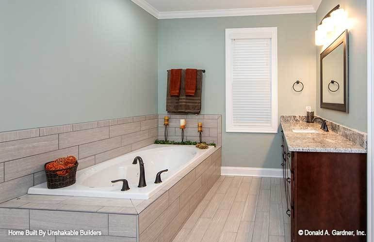 The primary bathroom includes a deep soaking tub with wrought iron fixtures and tile surround.