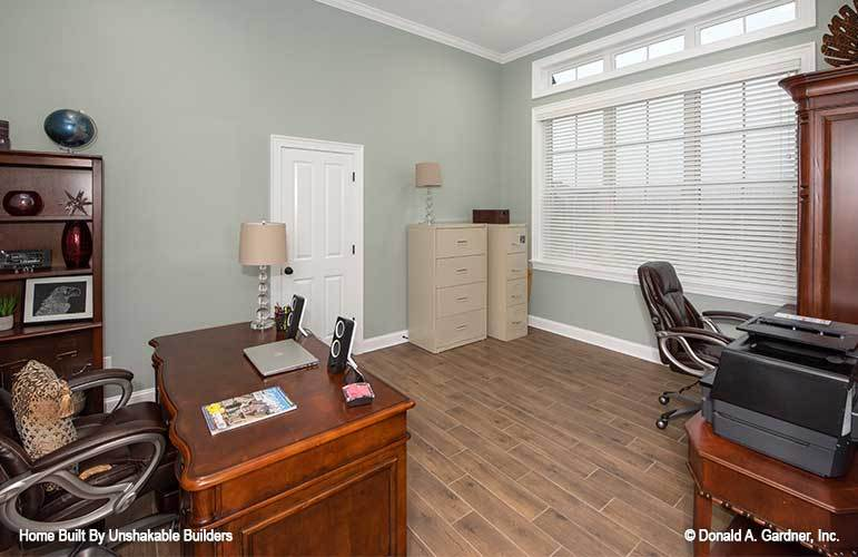 Study with wooden furnishings, leather swivel chairs, and three-paneled windows allowing natural light in.