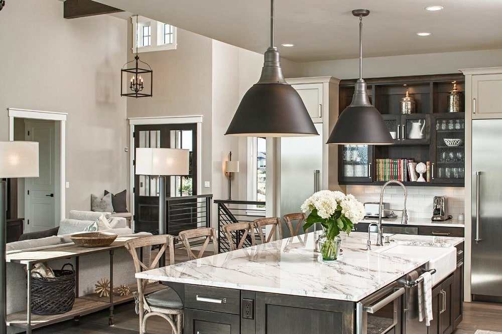 The kitchen has dark wood cabinets adjacent to the large island flanked with stainless steel appliances. These are contrasted by the white marble countertop and the stainless steel appliances.