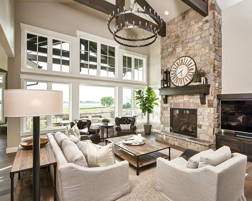 The living room offers gray upholstered seats, a rustic coffee table, and a stone fireplace with a round clock on top. These are then brightened by the large glass wall.