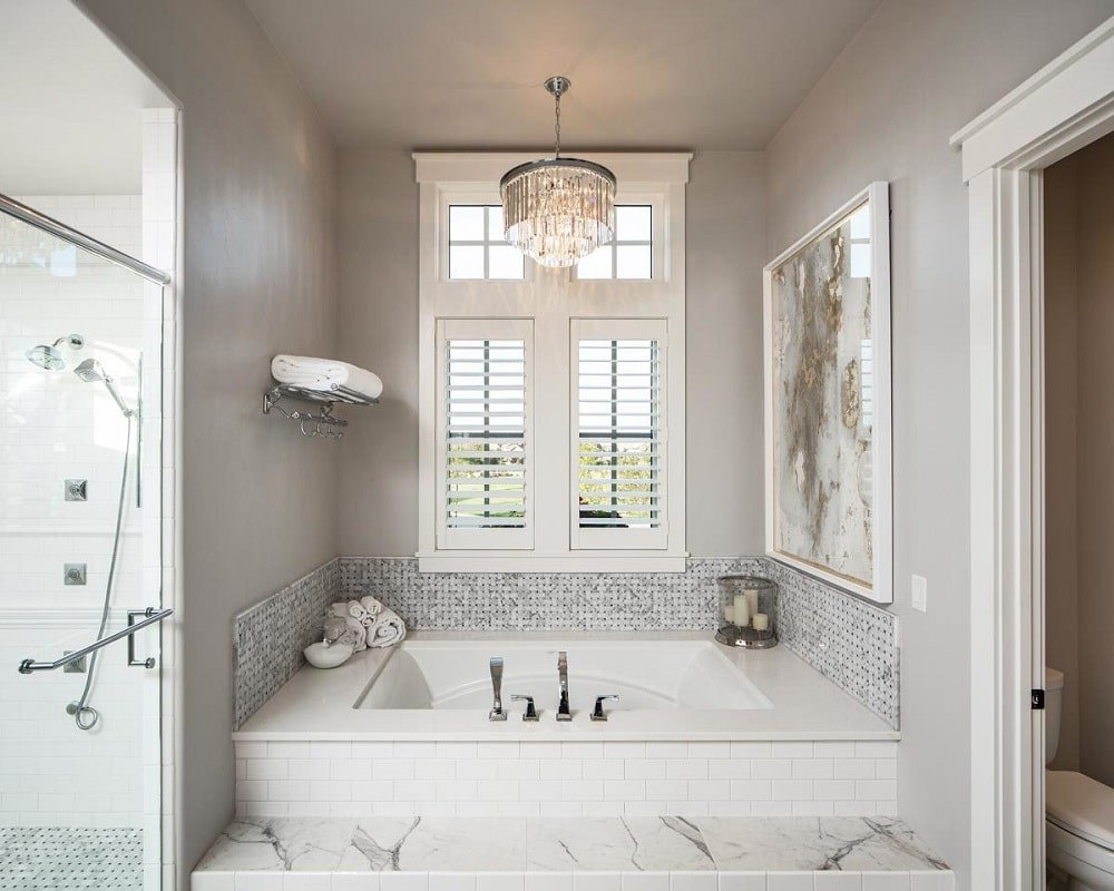 The primary bath is equipped with a water closet, a walk-in shower, and a deep soaking tub under the round crystal chandelier in an alcove by the window.