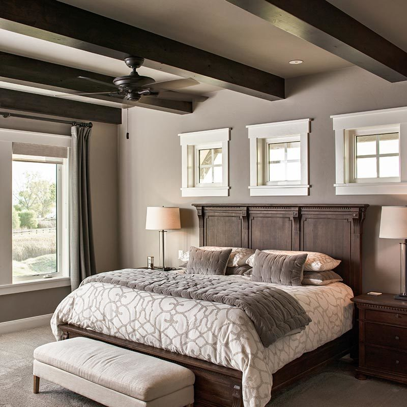 Primary bedroom with carpet flooring and a regular taupe ceiling lined with dark wood beams that match the wooden traditional frame of the bed along with the bedside drawers.