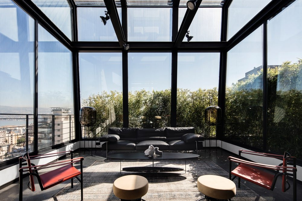 This is a sun room on the far edge of the living room area with glass walls and ceiling to bring in maximum natural lighting.
