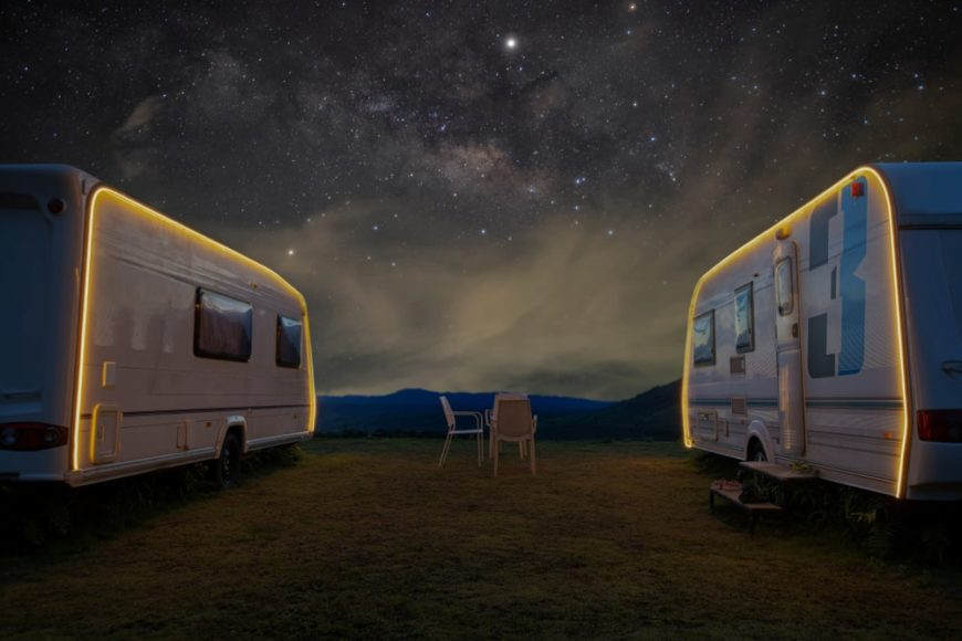 A close look at a couple of travel trailers parked at night.