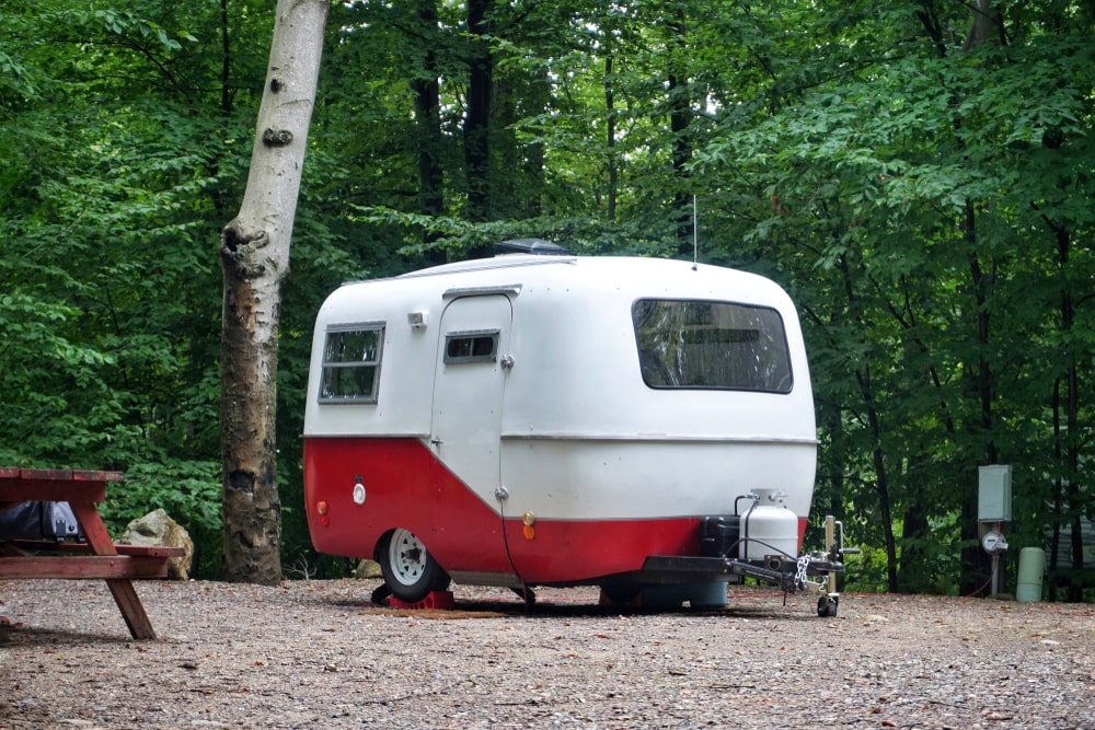 A look at a red and white scamp trailer parked near a forest.
