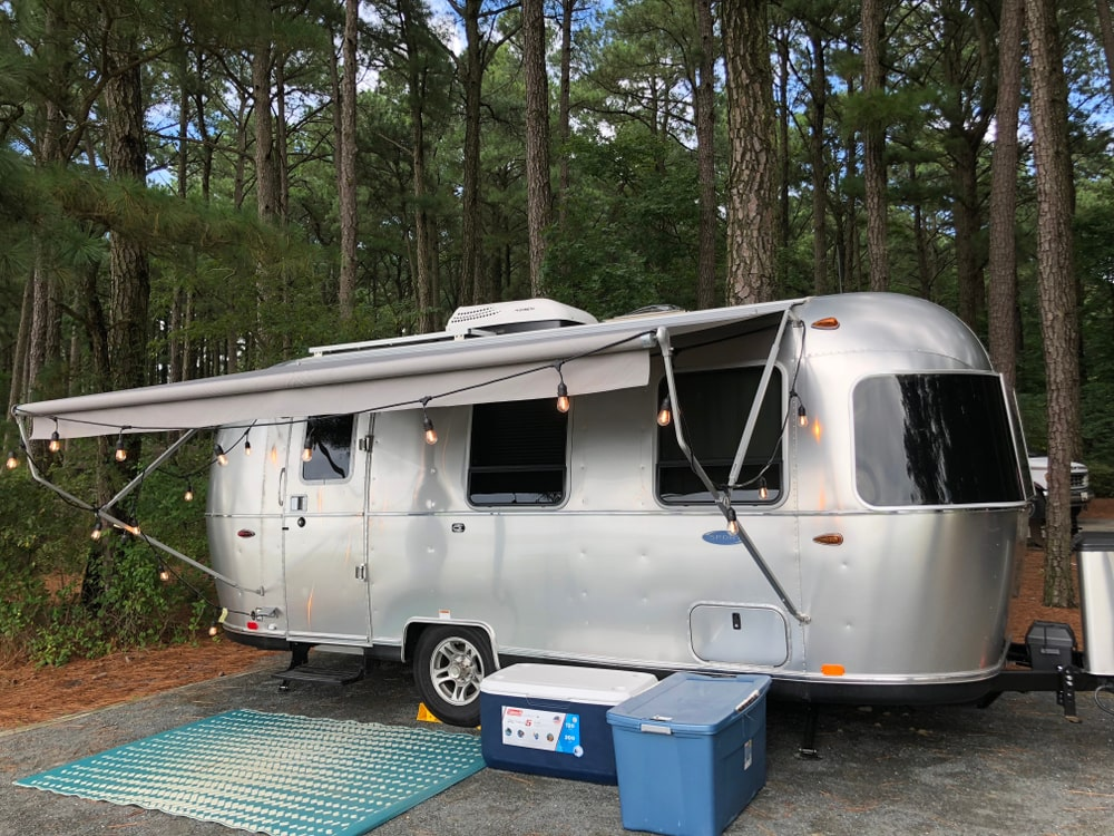 A silver stainless steel airstream travel trailer by a forest.
