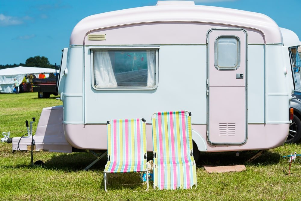 A small travel trailer with white and pink pastel tones that match the outdoor chairs.
