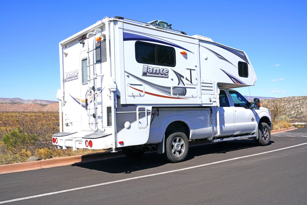 A white truck camper on the road.
