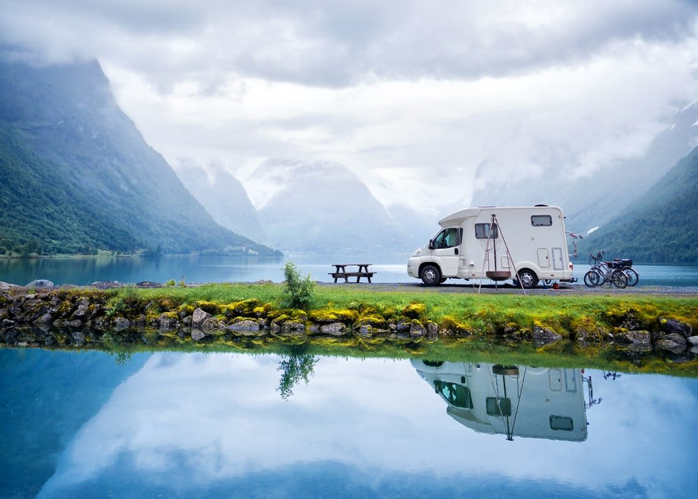 A small RV parked at a campground surrounded by water.
