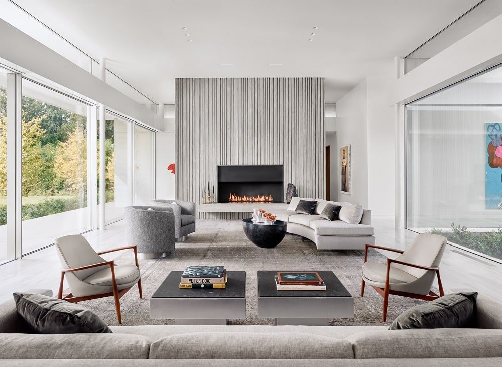 The living room has a modern fireplace on the far side across from the curved sofa.