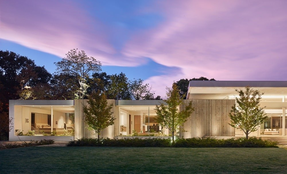 The warm glow of the house interiors pair well with the lighting of the landscape making the trees stand out.