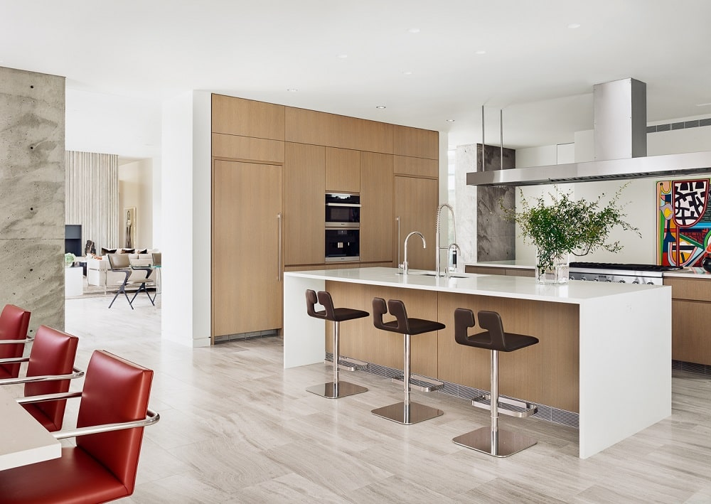 The kitchen has a large waterfall white kitchen island paired with brown wooden cabinetry and modern appliances.
