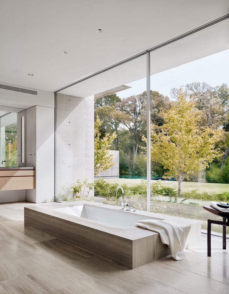 The primary bathroom showcases the large bathtub that is embedded into the ground by the large wall of glass that features a great view.
