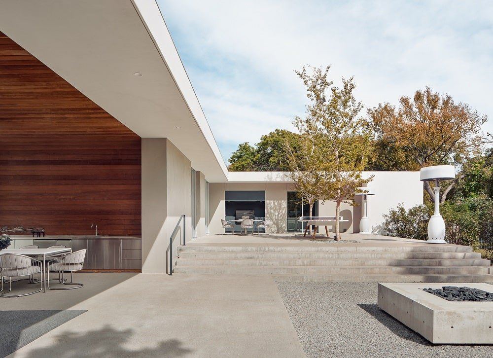 This is a view of the courtyard with a concrete floor, a fire pit and large open wall that combine the interior and exterior.