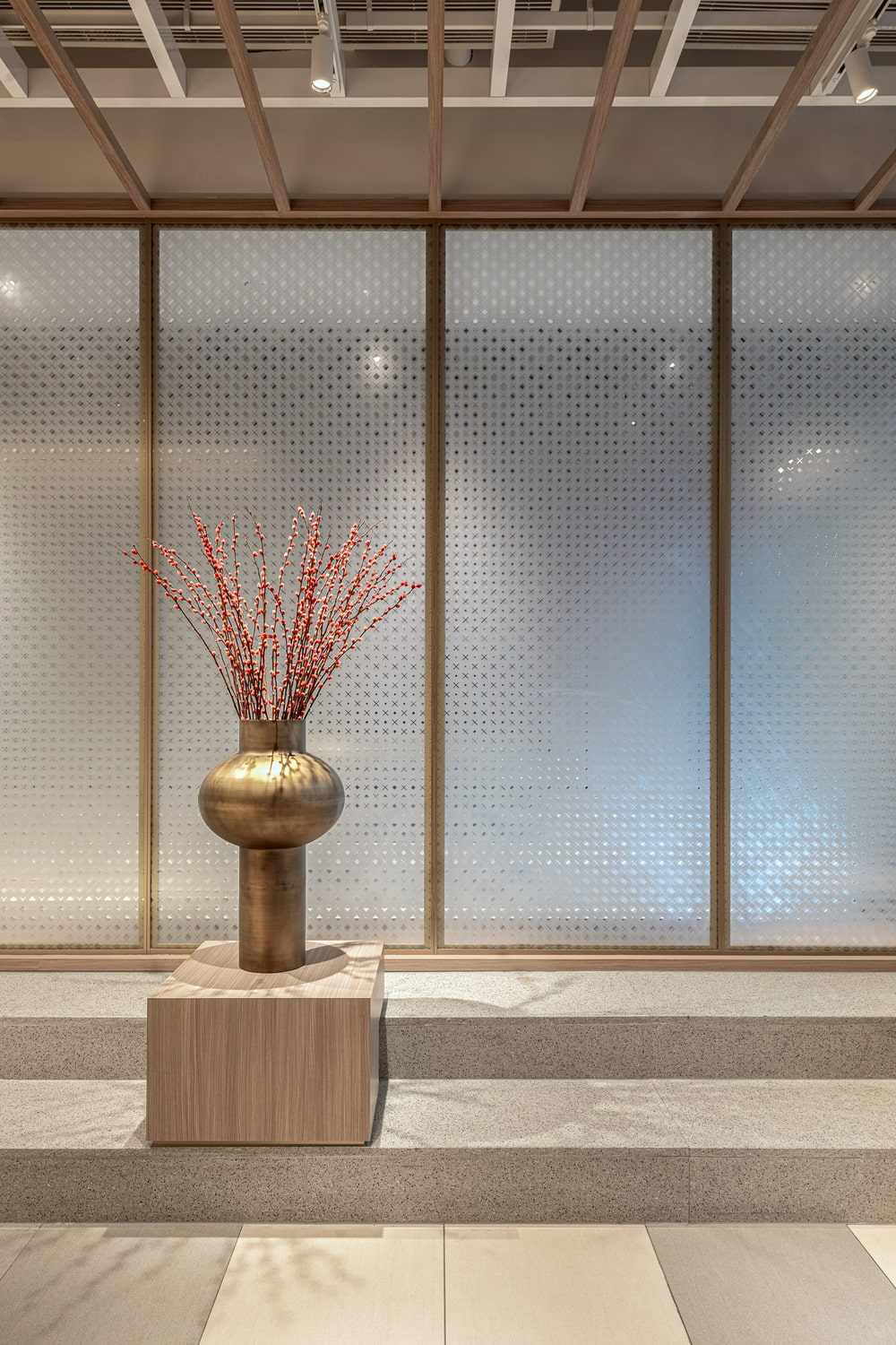 This is a close look at the swiveling frosted glass walls adorned with a wooden pedestal topped with a flower vase display.