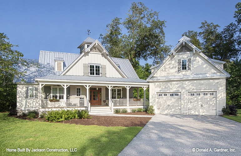 This is a front view of the farmhouse with a wide concrete driveway leading to a couple of white garage doors that match the bright exterior walls of the house with a front porch.