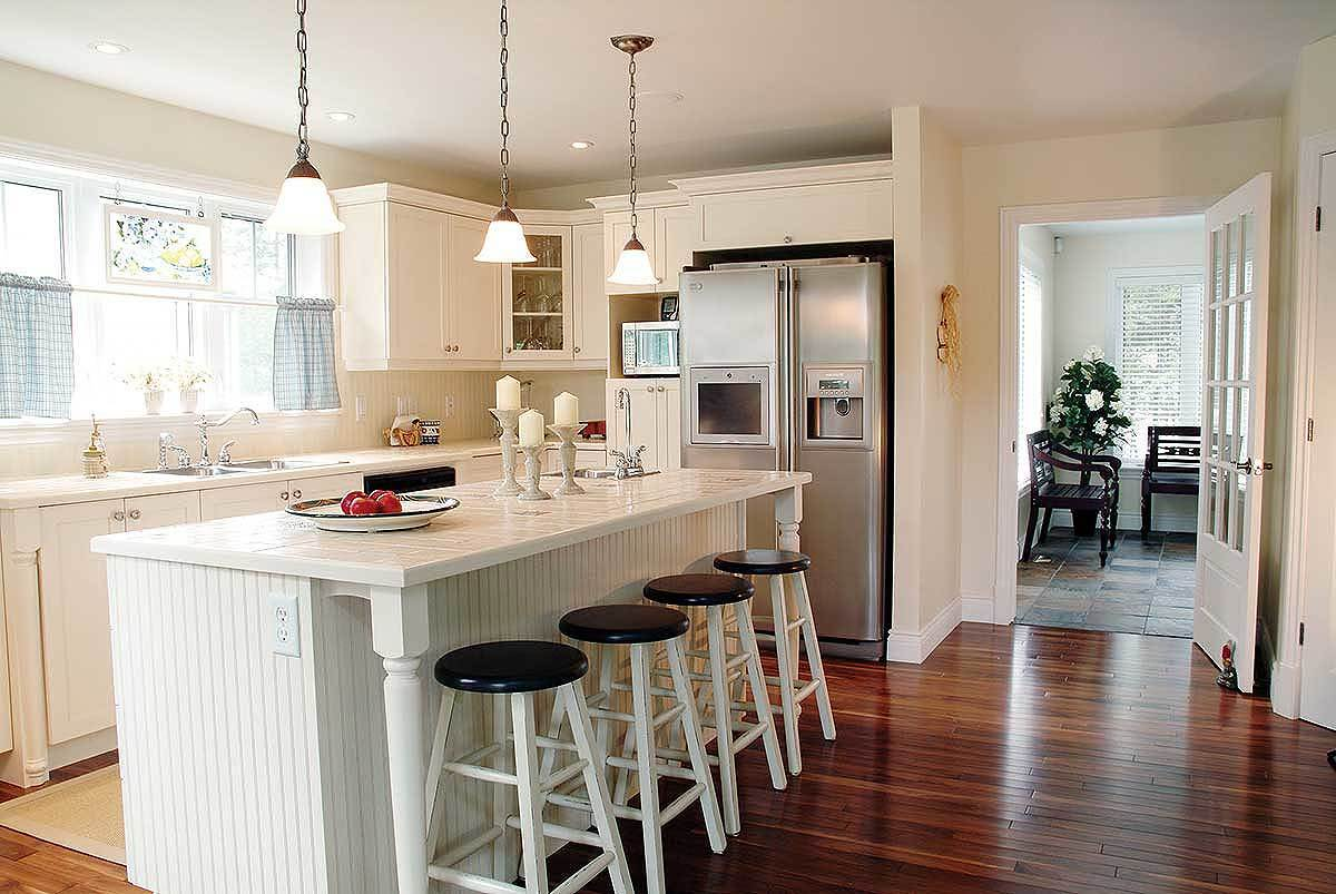Kitchen with white cabinetry, stainless steel appliances, and a breakfast island lined with round bar stools.