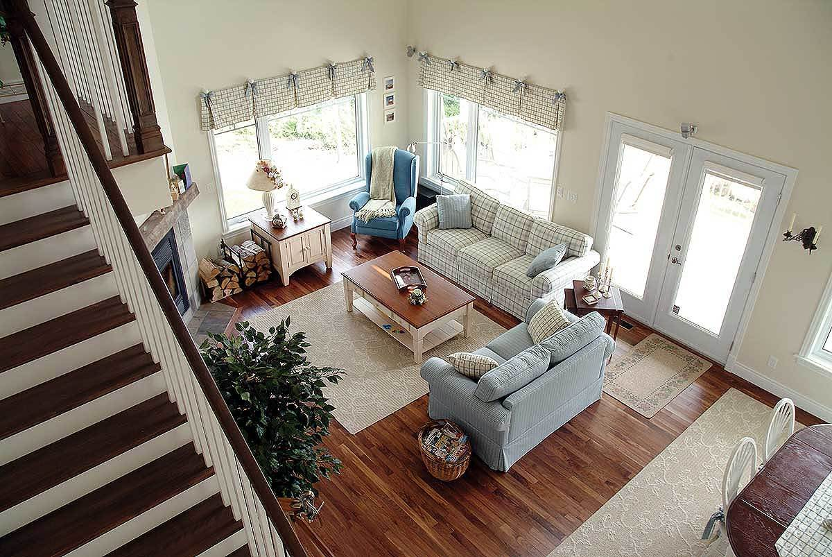 Living room with checkered sectionals, a blue wingback chair, wooden tables, and a corner fireplace.