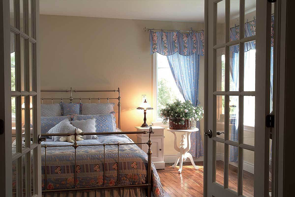 Primary bedroom with a french door, a metal bed, and white tables over the hardwood flooring.